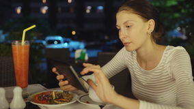 Happy woman using smartphone and messaging sitting in restaurant at night stock video