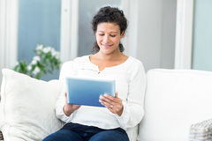 Happy woman using tablet computer. Happy pregnant woman using tablet computer on sofa stock photography