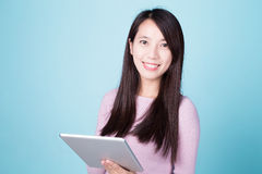 Happy woman using tablet pc. On blue background, asian beauty Stock Photo