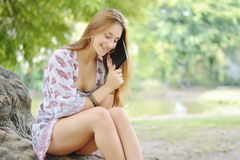 Happy woman using tablet pc in the park. Stock Photography