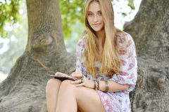 Happy woman using tablet pc in the park. Royalty Free Stock Photo