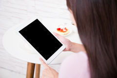 Happy woman using tablet pc. Happy woman sitting and using tablet pc at home, asian beauty Royalty Free Stock Images