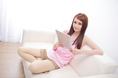 Happy woman using tablet pc on sofa. In the living room, asian beauty Stock Photography