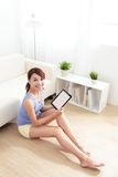 Happy woman using tablet pc on sofa. In the living room, empty computer screen is great for your design copy space, asian beauty Stock Photo