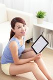 Happy woman using tablet pc on sofa. In the living room, empty computer screen is great for your design copy space, asian beauty Stock Photos