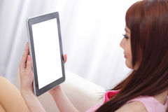 Happy woman using tablet pc on sofa Royalty Free Stock Photo