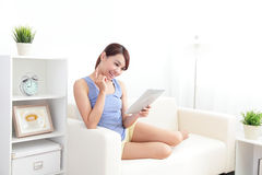 Happy woman using tablet pc on sofa. In the living room at home, asian beauty Royalty Free Stock Photos