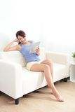 Happy woman using tablet pc on sofa Royalty Free Stock Photos