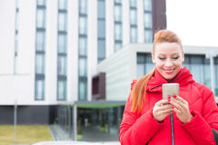 Happy woman using texting on smart phone outdoors on a city building background Stock Photo