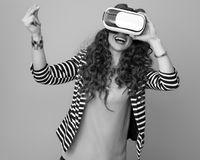 Happy woman using virtual reality gear and snapping fingers Stock Photography
