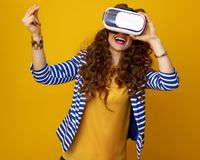 Happy woman using virtual reality gear and snapping fingers. Happy stylish woman with long wavy brunette hair against yellow background using virtual reality Royalty Free Stock Images