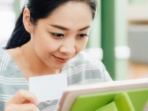 Happy woman is using a white mockup credit card for online shopping on tablet. Happy Asian woman is using a white mockup credit card for online shopping on stock photo