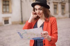 Happy woman on vacation with map, traveler walks the city. Sunny day. Back view. A young tourist woman in a hat, red jacket. stock photography
