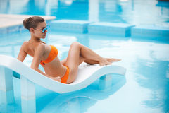 Happy woman on vacation near the blue pool Royalty Free Stock Images