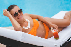 Happy woman on vacation near the blue pool Royalty Free Stock Photos