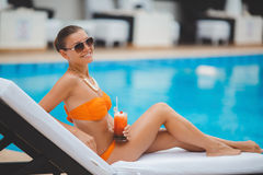 Happy woman on vacation near the blue pool Stock Photography