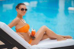 Happy woman on vacation near the blue pool Stock Image