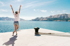 Happy woman on vacation standing by the sea. Arms raised. Carefree young female enjoy vacation. Royalty Free Stock Photos