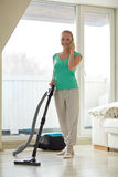 Happy woman with vacuum cleaner at home Royalty Free Stock Image