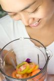 Happy woman with vegetables in a blender royalty free stock image