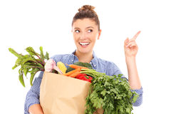 Happy woman with vegetables pointing at something. A picture of a happy woman with vegetables pointing at something over white background stock photography