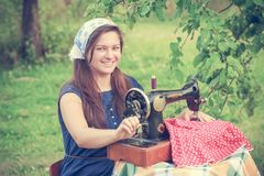 Happy woman with vintage hand sewing machine Stock Photos