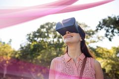 Happy woman in VR headset looking at pink lights interface. Digital composite of Happy woman in VR headset looking at pink lights interface Royalty Free Stock Images