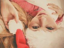Happy woman wearing pajamas and Santa Claus hat Royalty Free Stock Photos