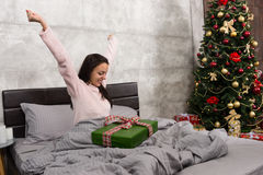 Happy woman wake up and rejoice at her christmas present while s Stock Image