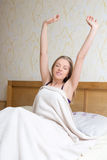 Happy woman waking up and stretching her arms up Royalty Free Stock Photos