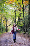 Happy woman on walk. A smiling, very happy young woman walking under colorful fall foliage stock photo
