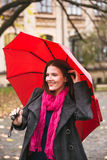 Happy woman walking in autumn city park. Rainy weather and yellow trees around Stock Photos