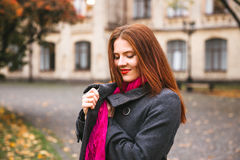 Happy woman walking in autumn city park. Rainy weather and yellow trees around Royalty Free Stock Image
