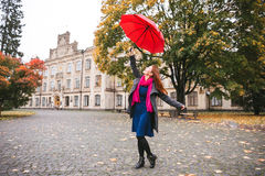 Happy woman walking in autumn city park. Rainy weather and yellow trees around.  Royalty Free Stock Photo
