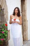 Happy woman walking with flower in hand Royalty Free Stock Photography