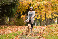 Happy woman walking her Golden Retriever Dog in a park with Fall Stock Photo