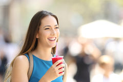 Happy woman walking and holding a slush. Single happy woman walking and holding a slush in the street Stock Images
