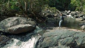 Happy woman walking jungle. Hiking outdoors on nature - happy woman walking through beautiful jungle. Walking the rocks near waterfall stock footage