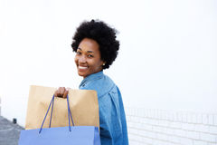 Happy woman walking with shopping on sidewalk Royalty Free Stock Images
