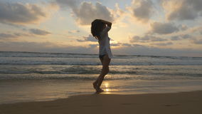 Happy woman walking and spinning on the beach near the ocean. Young beautiful girl enjoying life and having fun at sea Royalty Free Stock Image