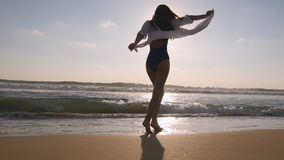 Happy woman walking and spinning on the beach near the ocean. Young beautiful girl enjoying life and having fun at sea Royalty Free Stock Photography