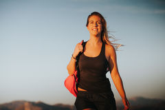 Happy woman walking with a sports bag on the shoulder. Sports concept Stock Image
