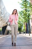Happy woman walking and talking on cellphone in the city Royalty Free Stock Images