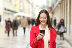 Happy woman walking using a cellphone in the street. Happy woman in red walking towards camera using a cellphone in the street in winter stock photography