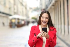 Happy woman walking using smart phone in the street. Front view of a happy woman in red walking using smart phone in the street in winter royalty free stock photo