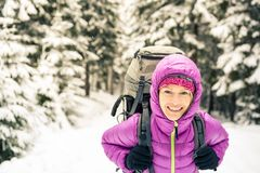 Happy woman walking in winter forest with backpack stock photography