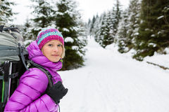 Happy woman walking in winter forest with backpack stock image