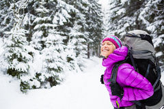 Happy woman walking in winter forest with backpack Stock Photo