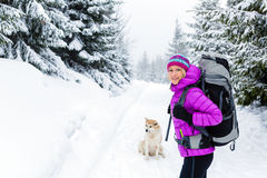 Happy woman walking in winter forest with dog Royalty Free Stock Images