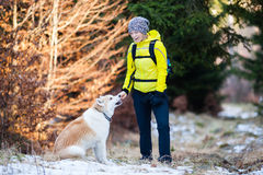 Happy woman walking in winter forest with dog Royalty Free Stock Photos